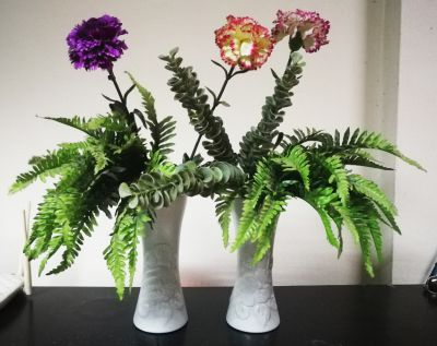 2 terracotta vases with plastic plants